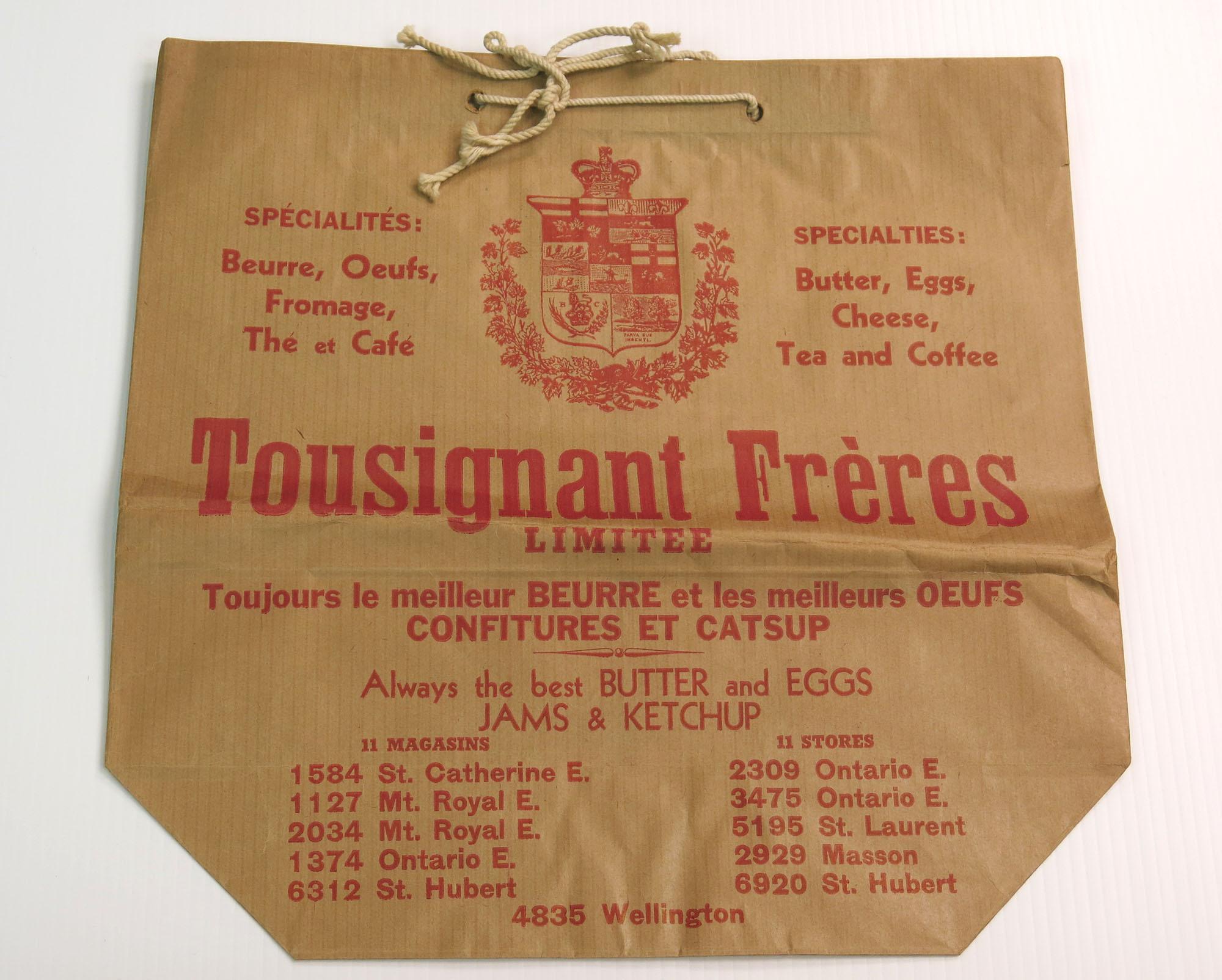Sac en papier brun, avec des écritures rouges, de l'épicerie Tousignant & Frères. Des poignées en corde beige sont insérées dans le rebord en haut du sac.
