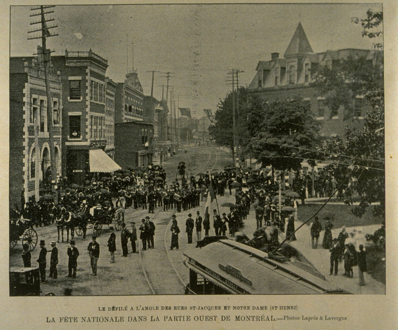Photo ancienne d'une foule sur une place lors d'un défilé où on aperçoit un tramway.