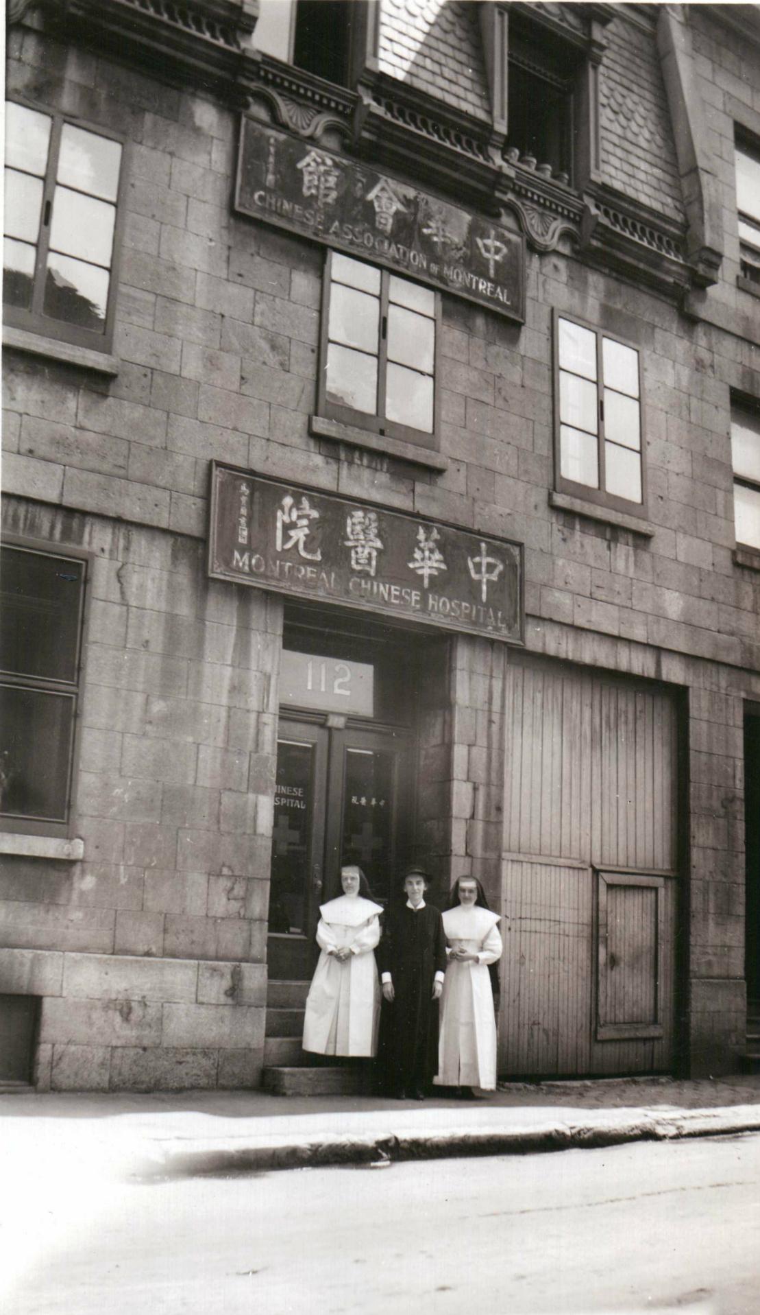 Deux religieuses posent devant la façade du nouveau local de l'hôpital chinois, au 112 rue De La Gauchetière.
