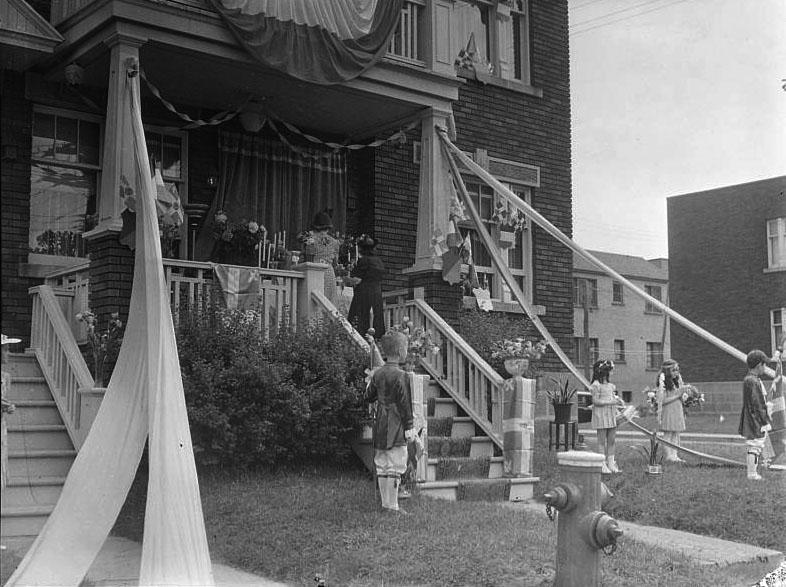 Deux garçons et deux fillettes se tiennent au bas du balcon d'une résidence décorée pour la Fête-Dieu. Sur le balcon, deux femmes déposent des fleurs sur un tabernacle.
