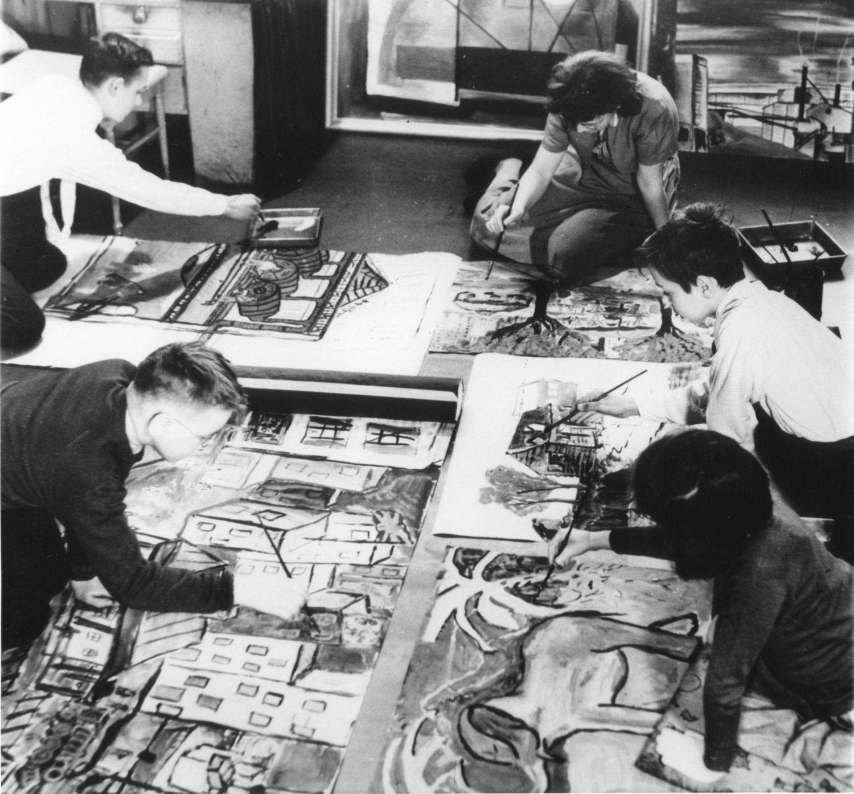 Photo en noir et blanc de quatre enfants et une femme qui peignent sur des toiles sur le plancher d'un appartement