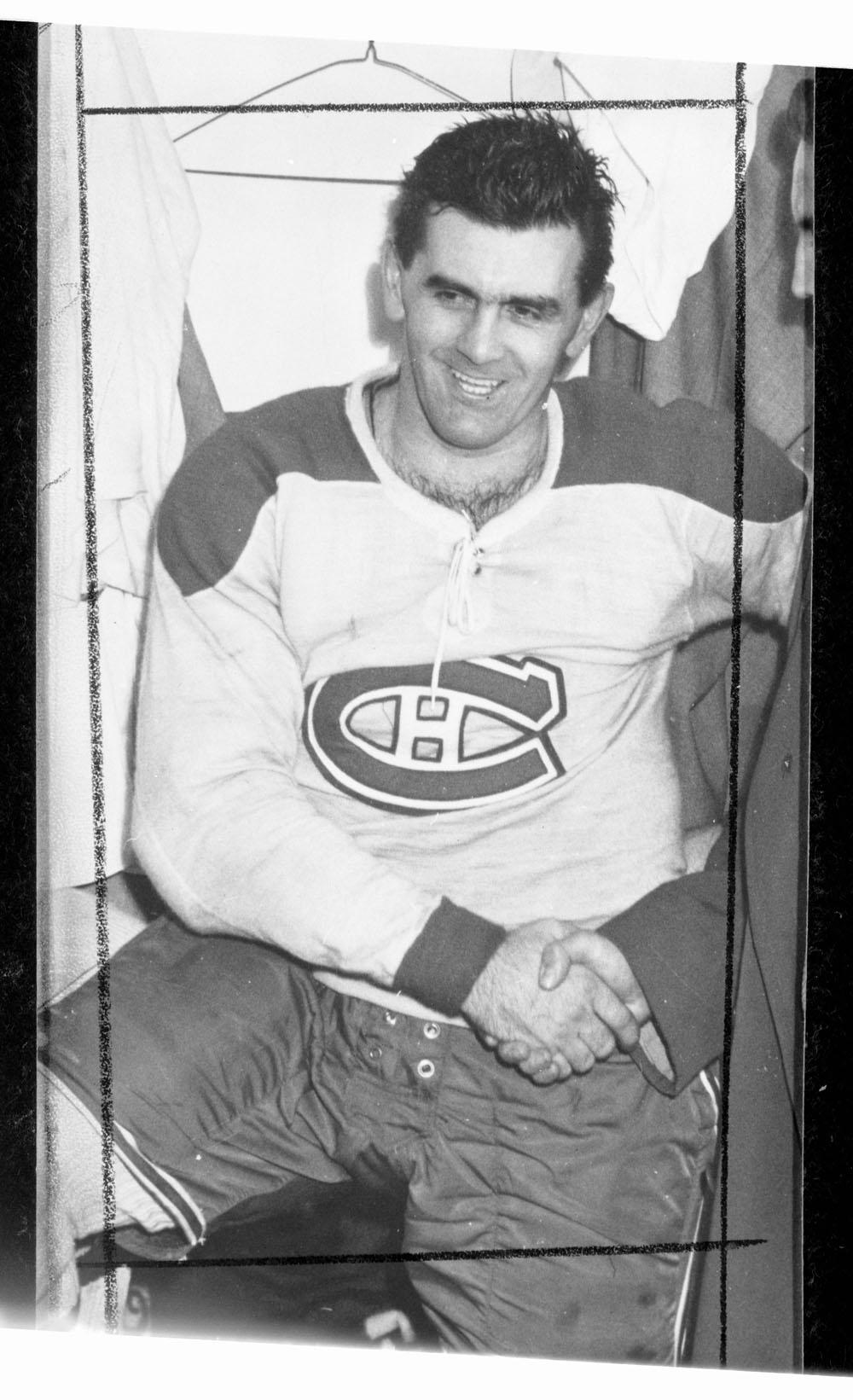 Photographie de Maurice RIchard souriant et serrant la main d'une homme.