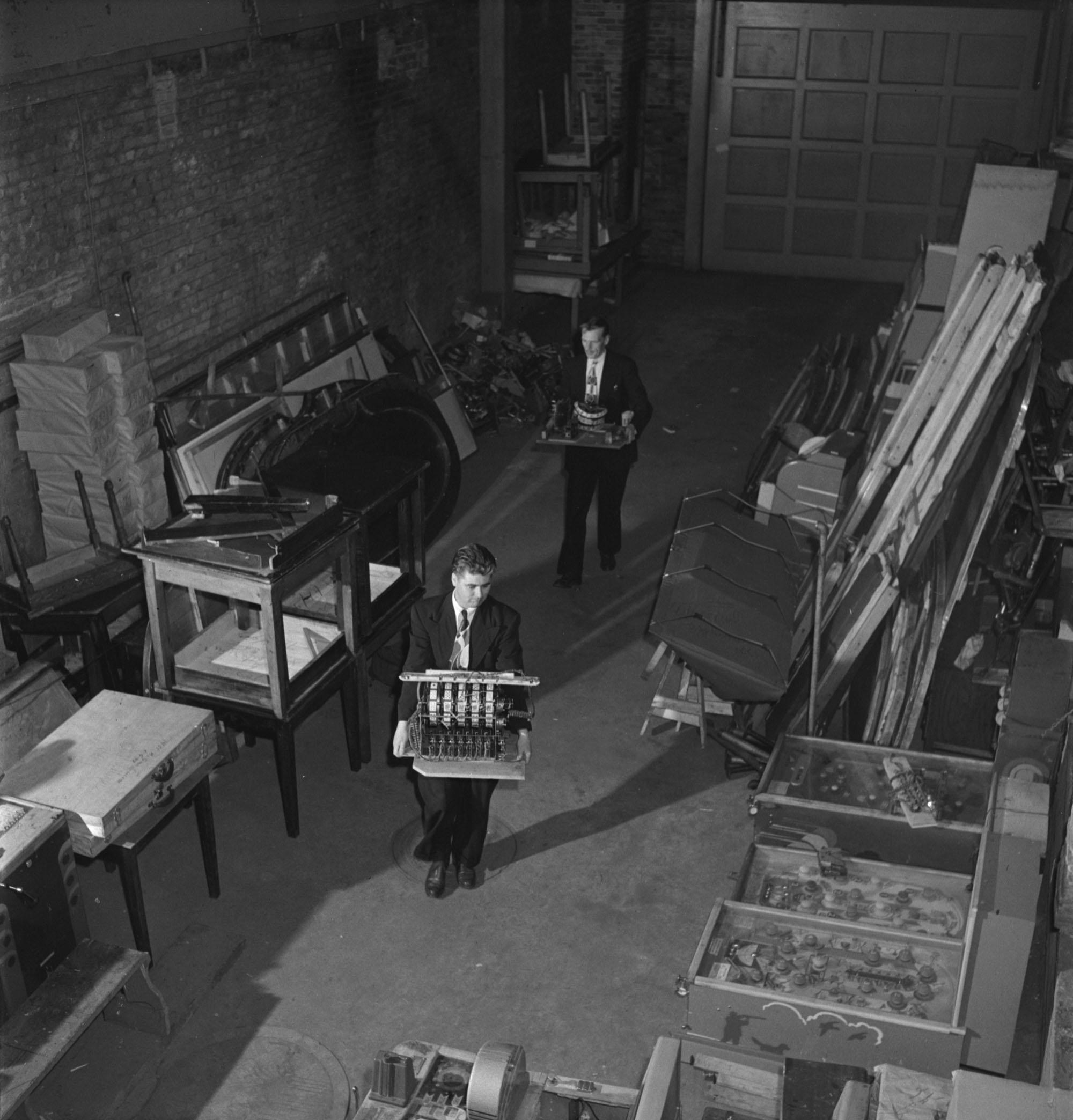 Intérieur d'un entrepôt. Deux hommes tiennent des machines dans leurs mains. De chaque côté, du matériel est empilé.