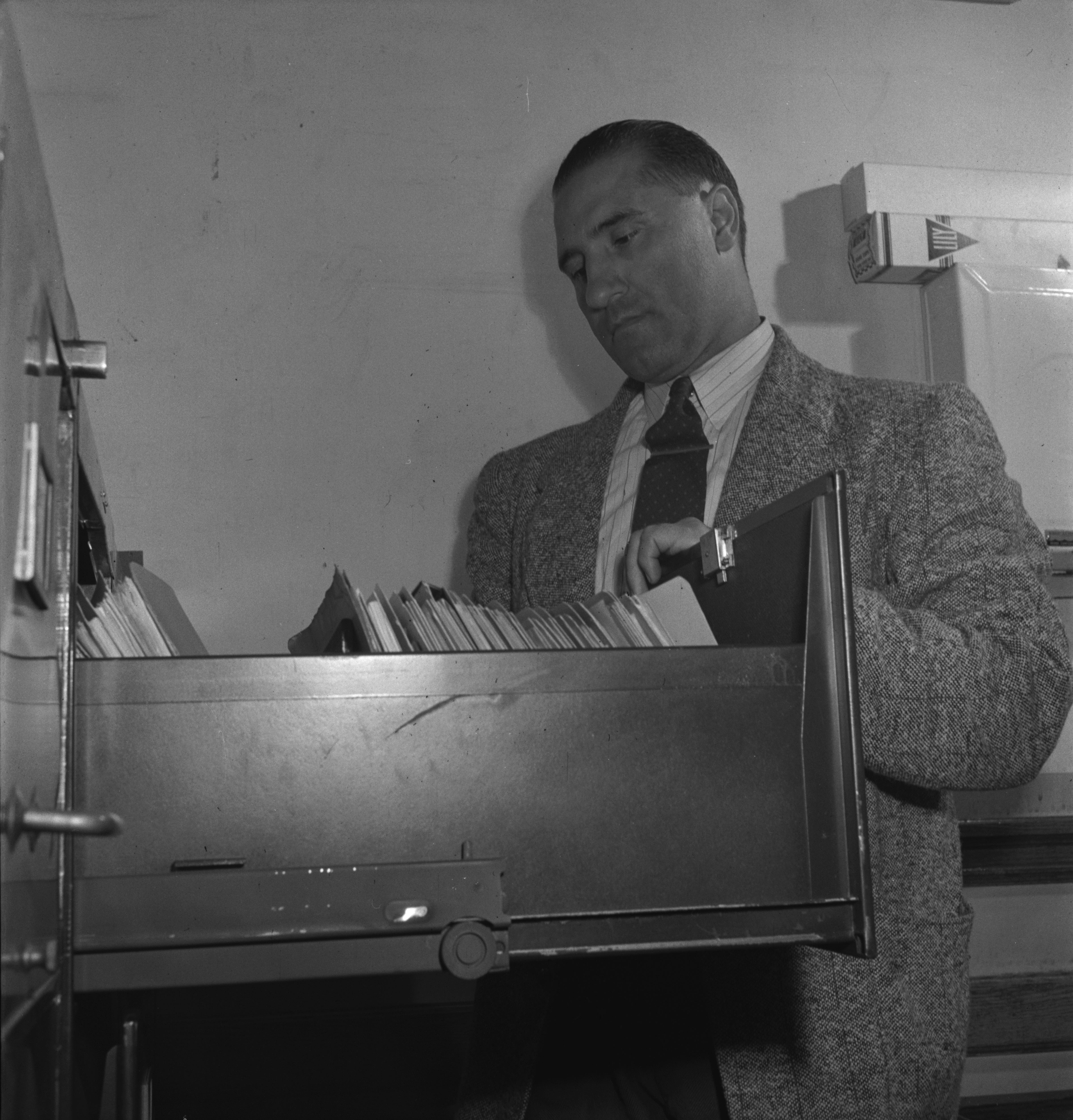 Photographie en noir et blanc d'un homme se tenant debout derrière un classeur.