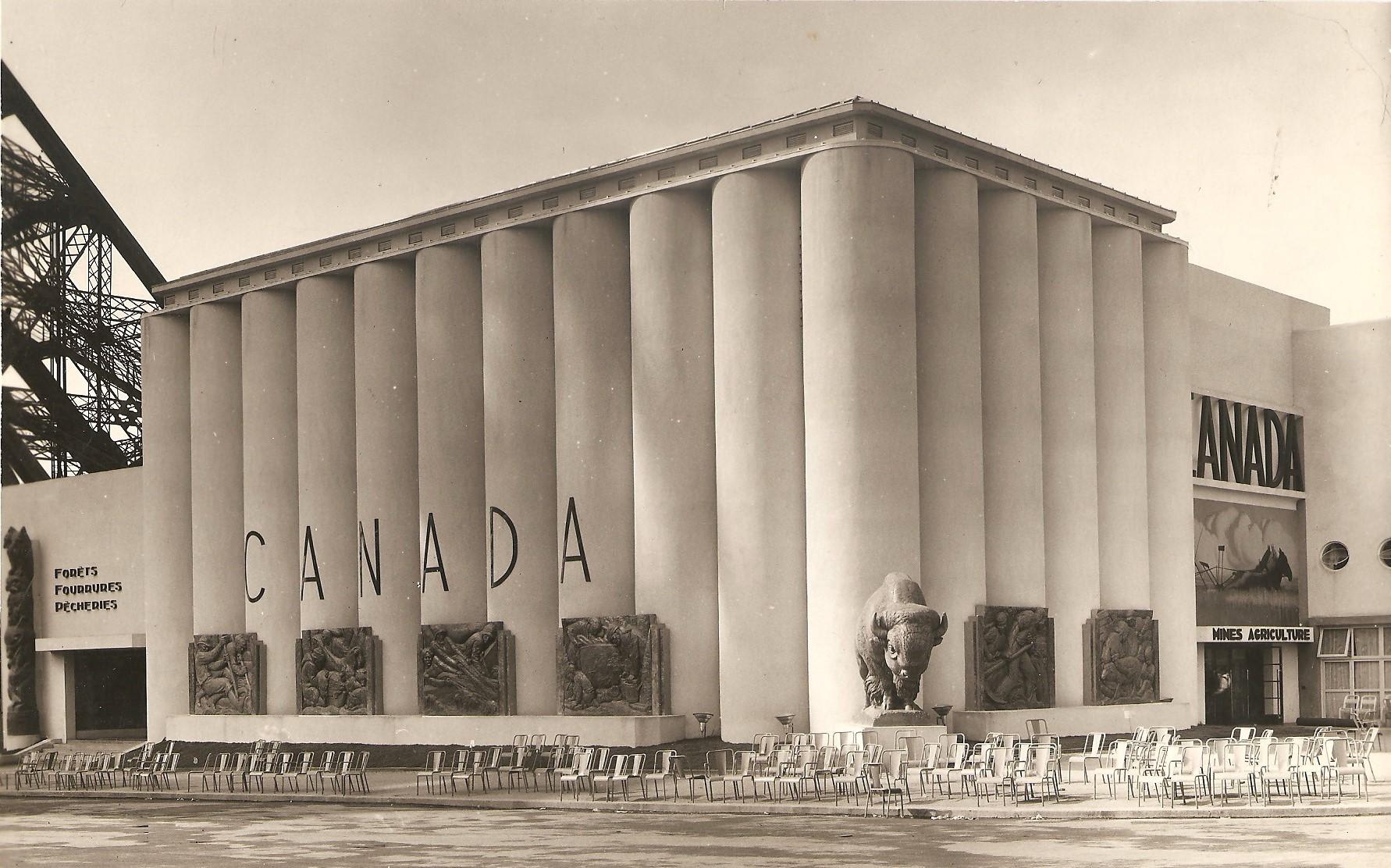 Photographie du bâtiment ayant abrité le pavillon du Canada, devant lequel il y a une statue de bison. On peut lire les inscriptions « Forêts fourrures pêcheries» (à gauche) et «Mines agriculture» (à droite).