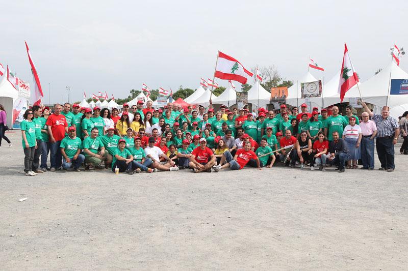 Près d'une centaine de personnes rassemblées pour une photo. Certain d'entre eux tiennent des drapeaux du Liban