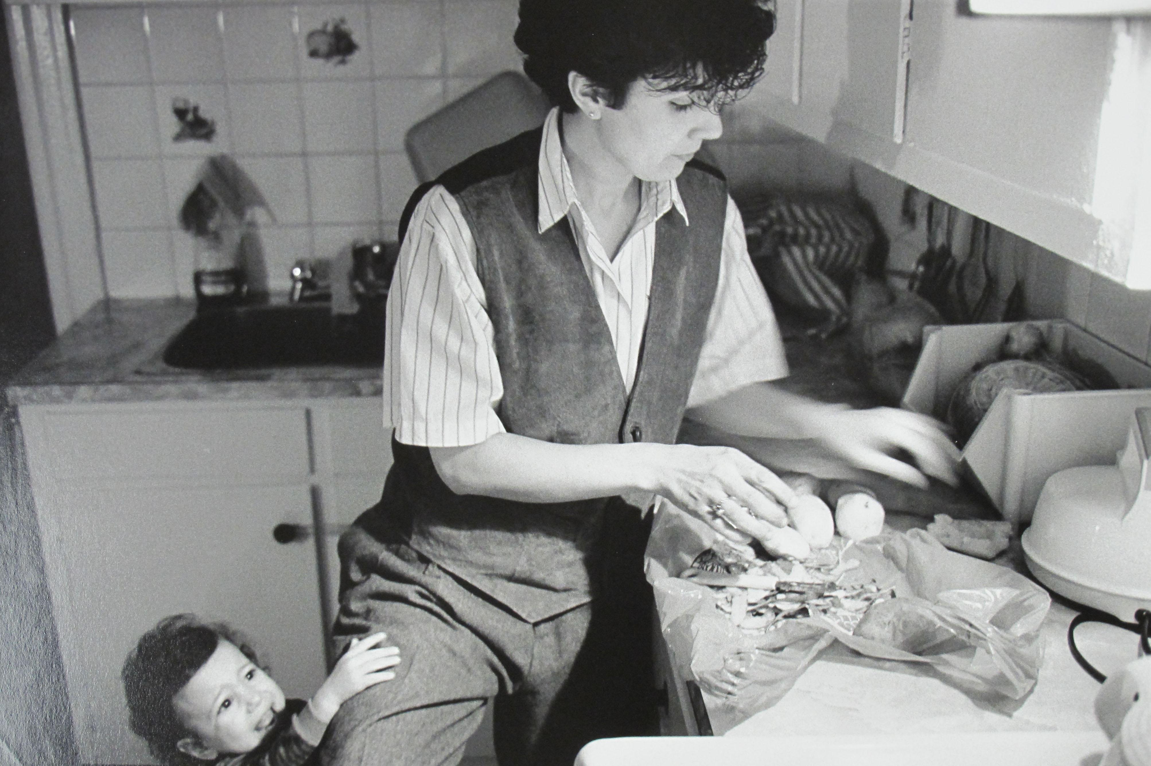 Une femme cuisine. Son jeune enfant est derrière elle et lui touche la jambe.