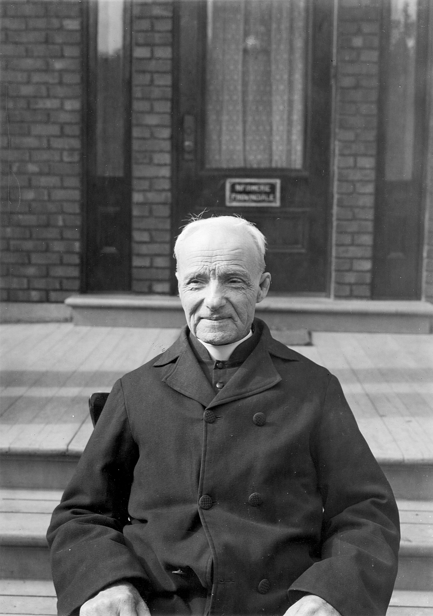 Portrait de frère André devant l'infirmerie provinciale vers 1925.