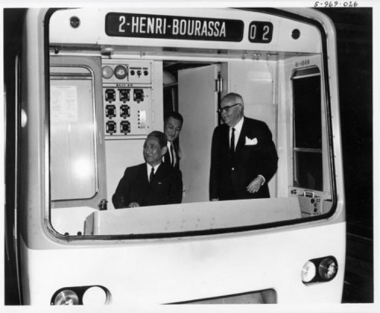 Deux ministres chinois et Lucien L'allier souriant dans un wagon de métro affichant «2 - Henri-Bourassa»