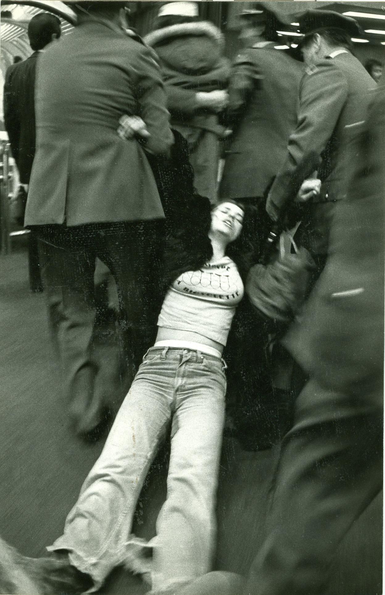 Claire Morissette est traînée au sol par deux policiers.