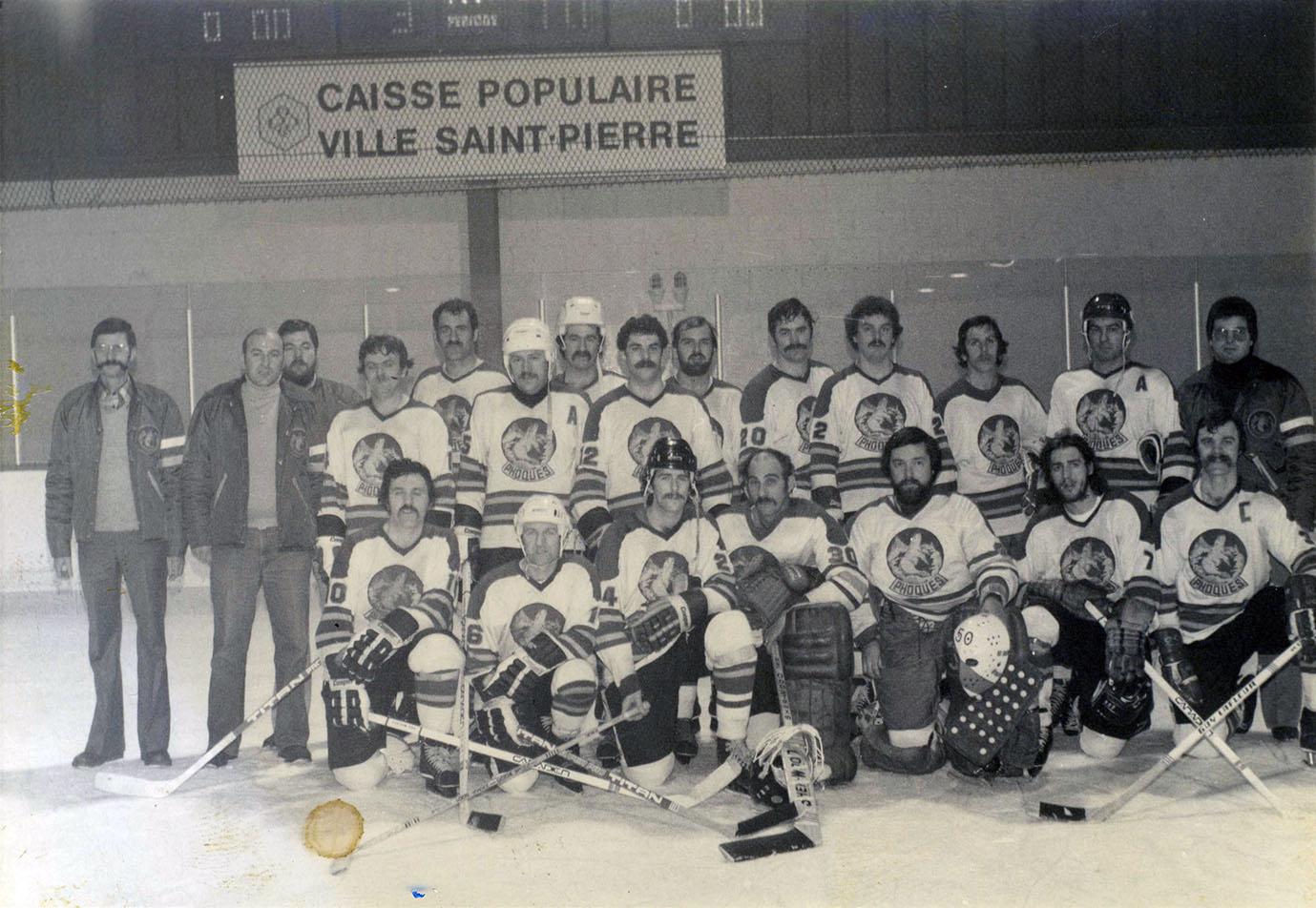 Sept hommes en habit de hockey sont agenouillés. Dix autres sont debout, entourés de quatre entraîneurs.
