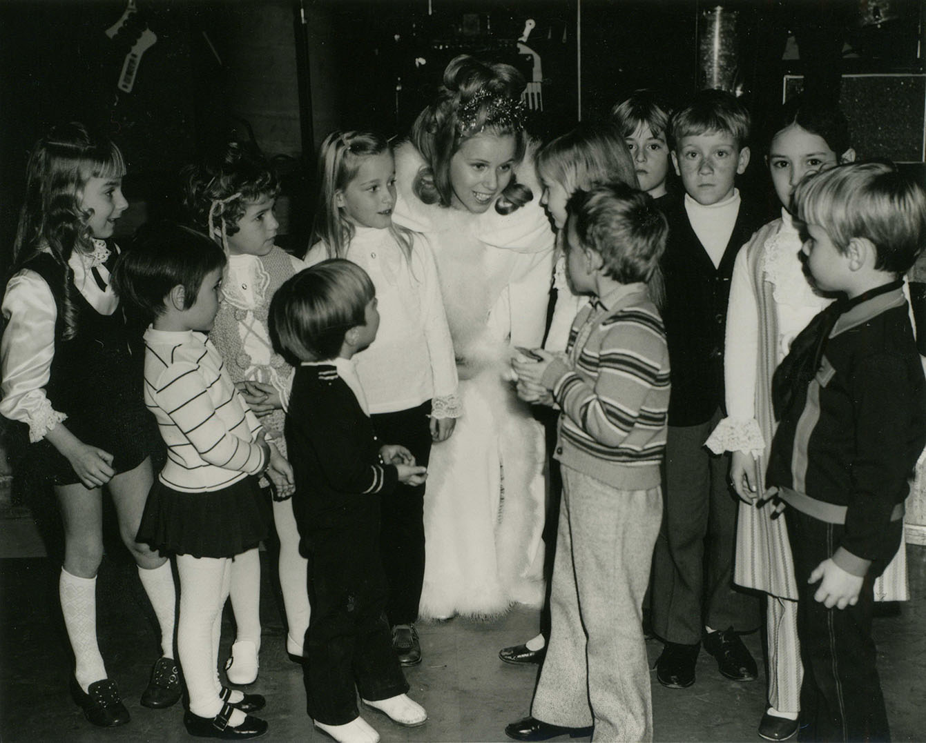 Une jeune femme, habillée en fée, est entourée d'enfants.