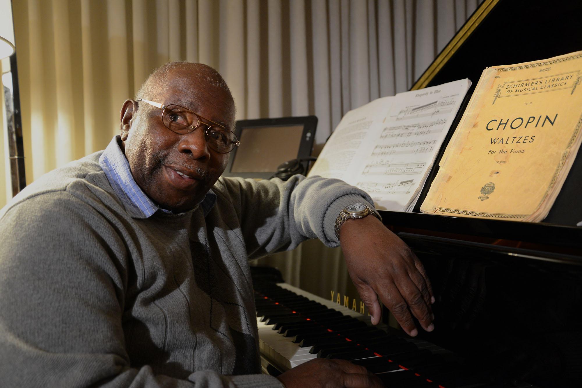 Photographie en couleurs, d'un homme noir assis devant un piano. Sur le piano est posée une partition de Chopin.