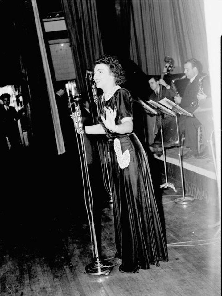 """La chanteuse Alys Roby accompagnée par un orchestre sur la scène d'une salle de spectacle lors de la radiodiffusion de l'émission """"Tourbillon de la Gaieté"""" de l'auteur Roger Marien par la station C.K.A.C. à Montréal."""