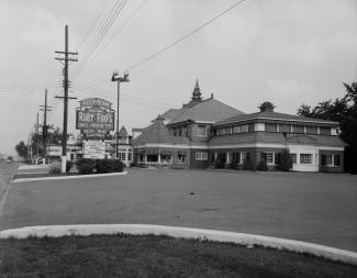 Photographie en noir et blanc d'un bâtiment le jour. À gauche, l'enseigne mentionne le nom du restaurant.
