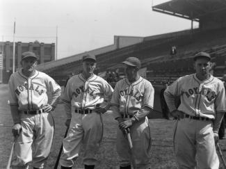 Photo en noir et blanc de quatre joueurs de baseball de l'équipe des Royals. Chacun s'appuie sur un bâton de baseball.