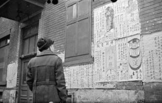Un homme lit des affiches en chinois sur le mur d'un édifice