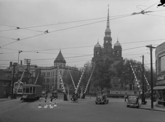 Photo ancienne d'une place où circulent un tramway et des voitures des années 1940 à un passage à niveau.