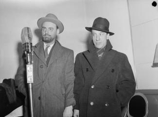 Photo en noir et blanc montrant deux comédiens. Devant eux, un micro.