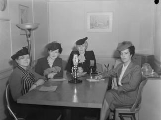 Photo noir et blanc de quatre femmes assises autour d'une table, un micro est posé au milieu de la table.