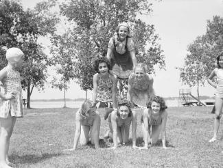 Six adolescentes forment une pyramide sur la pelouse d'un parc et deux autres jeunes filles les regardent