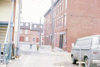 Scène de ruelle avec deux enfants et une rangée de maisons sur la droite