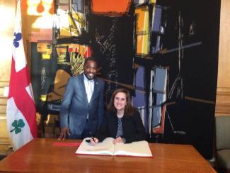 Angela Sierra signe le livre d'or de la Ville de Montréal en compagnie de Frantz Benjamin.