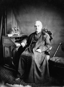 Photo du père Dowd assis sur un fauteuil.
