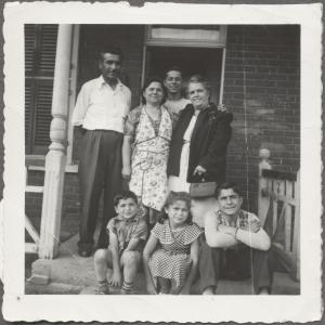 La famille Fratino sur le pas de la porte de leur maison sur la rue Clark. Ils sont quatre debout et trois enfants assis.