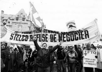 """Des travailleurs manifestent en brandissant une banderole portant l'inscription \""""Formation - Pension - Sécurité LA STELCO REFUSE DE NÉGOCIER\""""."""