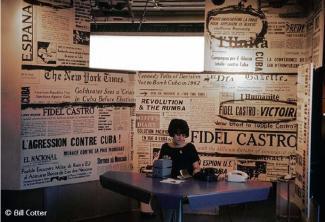 Une hôtesse assise devant une table avec derrière elle un mur tapissé d'articles de journaux évoquant différents moments de la révolution cubaine.