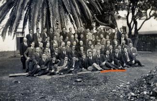 Photo en noir et blanc présentant un groupe d'hommes en veston-cravate répartis en cinq rangées prenant la pose devant un édifice et un palmier.