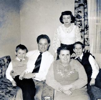 Manuel Jacome, un enfant assis sur ses genoux, une femme et un enfant à sa droite, et une femme debout derrière eux, dans un salon.