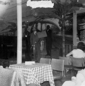 Deux musiciens et un chanteur sur une petite scène dans un café