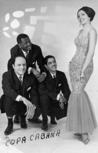 Trois hommes accroupis regardent une femme en robe de soirée à leur côté