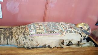Momie dans la vitrine du musée Redpath, elle présente de nombreuses décorations en cartonnage typiques de la période romaine de l'Égypte ancienne, dont le masque doré stylisé