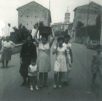 Trois femmes, un garçon et un enfant prennent la pose au milieu d'une rue d'une petite ville italienne