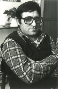 Photo d'un homme portant des lunettes, les bras croisés