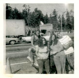 Groupe de quatre jeunes gens accotés sur une voiture sur le bord de l'autoroute
