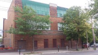 Photographie contemporaine d'un bâtiment de brique de trois étages.