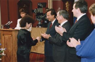 Aoura Bizzarri reçoit des mains du premier ministre Robert Bourassa la médaille de l'Ordre national du Québec à l'Assemblée nationale.