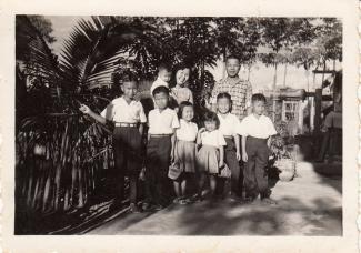 Photo en noir et blanc d'une famille de sept enfants avec la mère et le père. La mère tient le plus jeune dans ses bras.