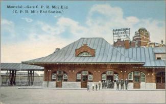 Carte postale colorée d'une petite gare de brique avec une dizaine de personnes devant, dont des enfants.