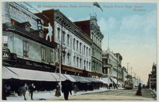 Carte postale colorisée montrant la rue Sainte-Catherine et les façades de magasins côté nord.