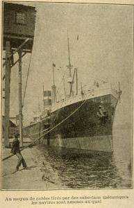 Photographie d'un employé débardeur tirant un bateau vers le quai du port.