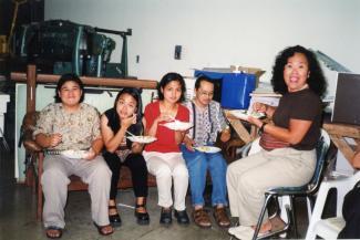 Cinq personnes d'origine philippine sont assis et mangent.