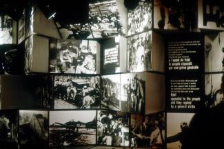 Des photographies représentant différents moments de la révolution cubaine ornent un mur aux faces irrégulières.