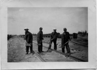 Quatre travailleurs pour une compagnie de chemin de fer en juin 1953.
