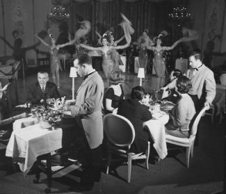 Intérieur de cabaret avec spectacle sur la scène, couples attablés et serveurs.