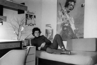 Un jeune homme portant col roulé et bottillons prend la pose sur son lit dans sa chambre à la résidence de l'Université. Il y a des affiches sur les murs.
